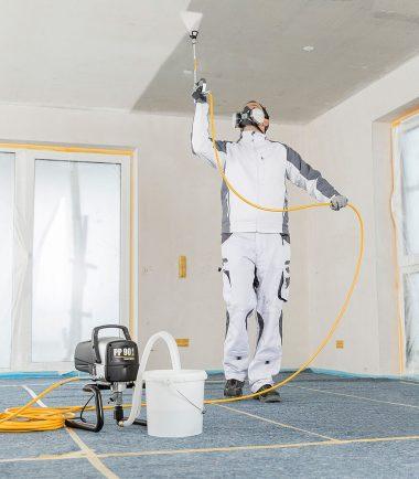 Man using PowerPainter 90 Extra Skid Spraypack on ceiling - SprayQuip Limited